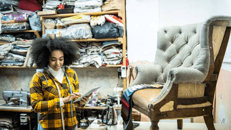 Woman of colour looking at a fabric card and deciding on which fabric for reupholstering a wingback chair