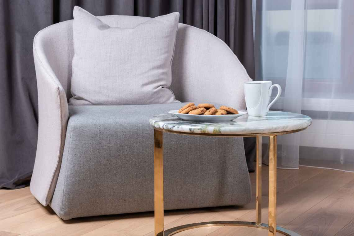 plate of crunchy cookie and cup of coffee placed near armchair in living room