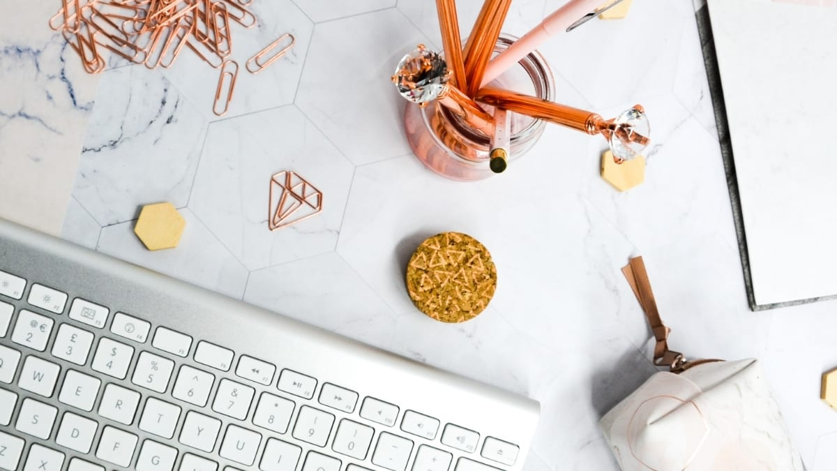 Square marble background with silver keyboard, jar of copper pens and pencils, scattered papers and copper paperclips and pencil case for use as April 2021 Advertisers post feature image
