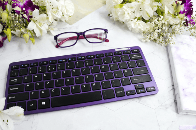 Black keyboard with purple lining set on a white marble desk decorated with flowers and seeing glasses beside it for preparing to return to work