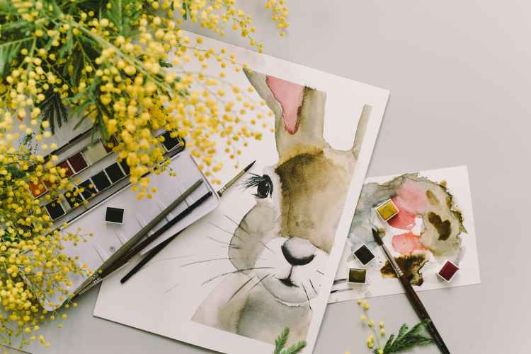 painting of a bunny beside yellow flowers for April 2021