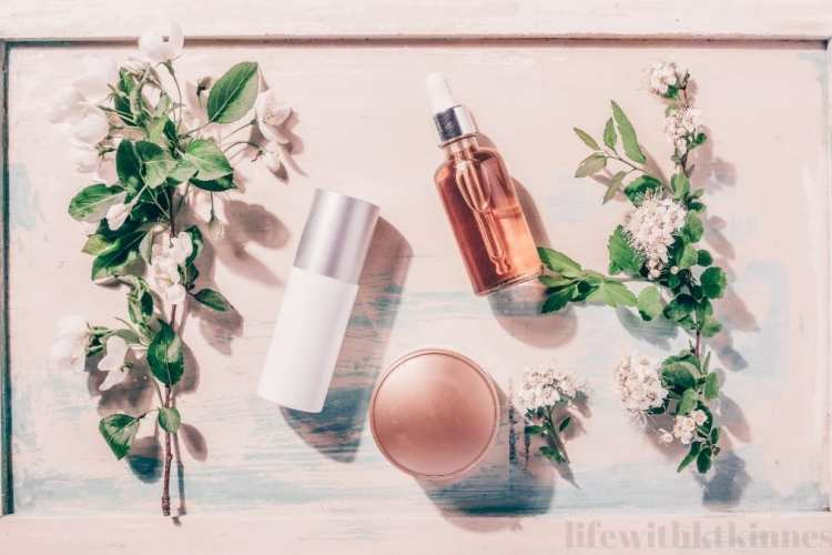 skincare products against a blush pink background with green foliage around the sides