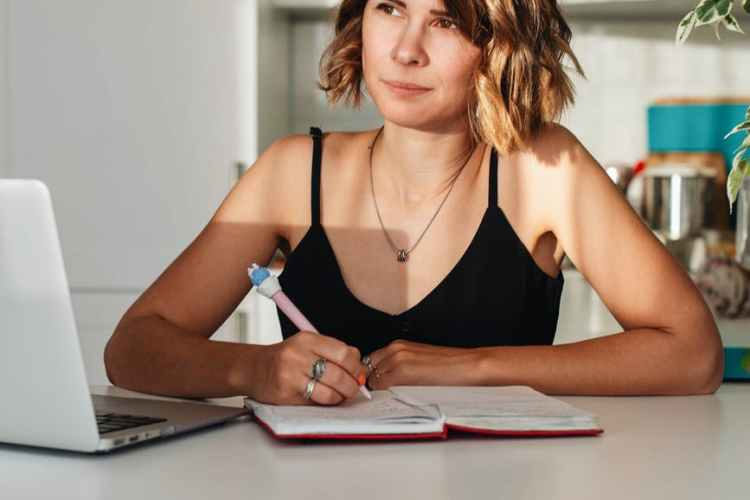 a businesswoman taking notes on her notebook from an academic editing service