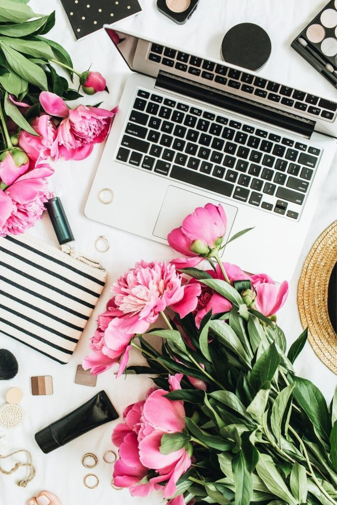 laptop and flatlay of flowers and makeup for blogging through the ages