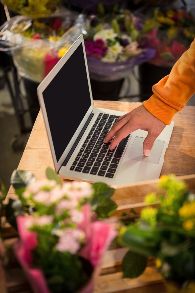 Laptop set on a counter surrounded by flowers