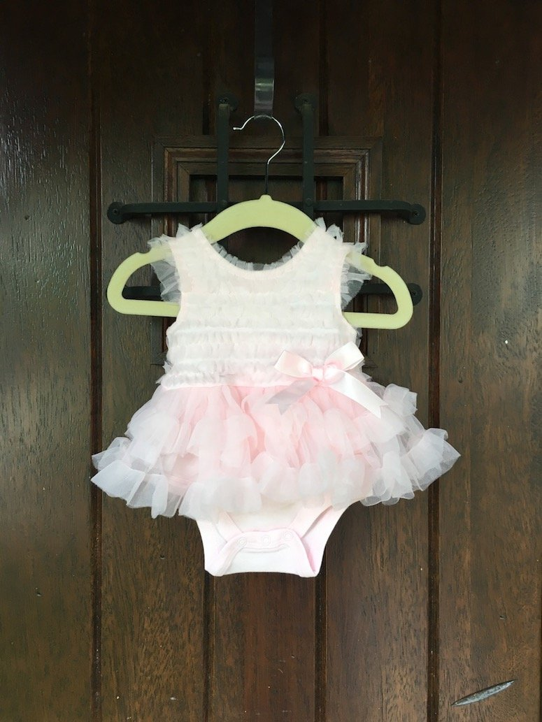 girl baby shower ideas hang outfit at front door to welcome guests. Click to see more from this beautiful Winnie the Pooh themed baby shower