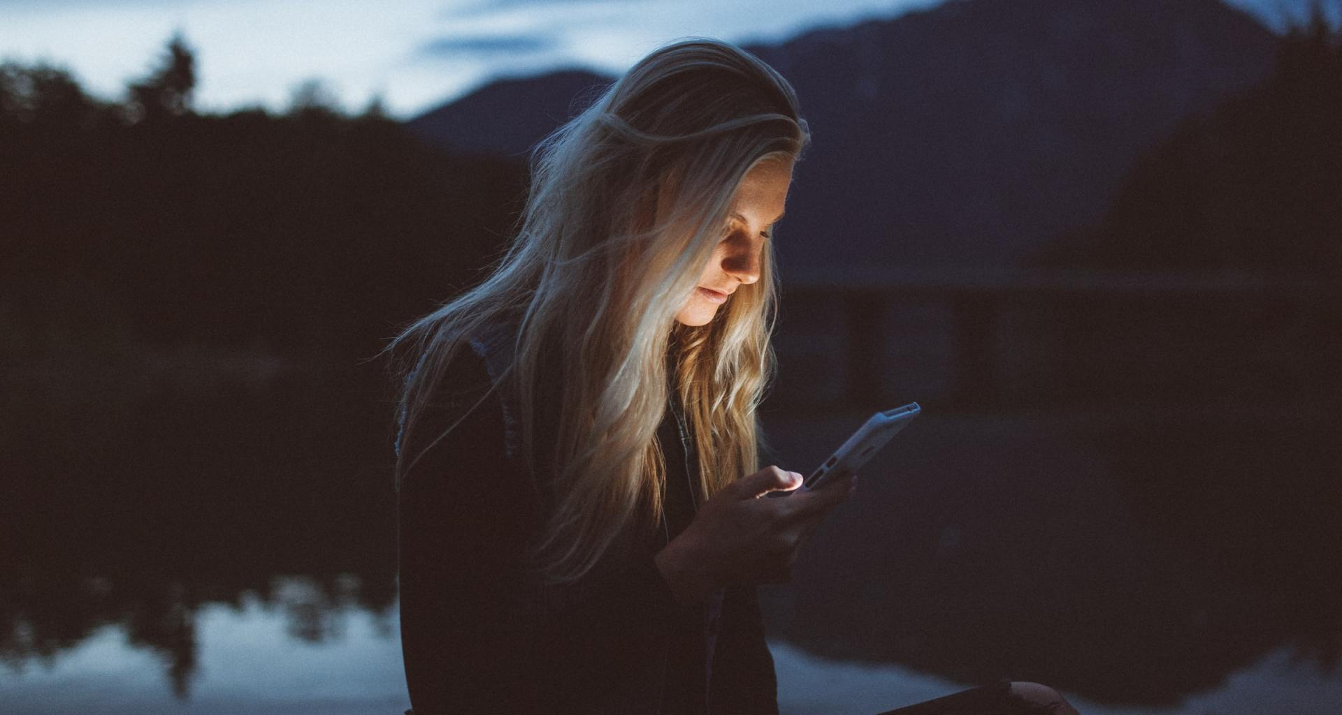 Blonde woman sitting and texting girl using an iPhone late evening at seaside