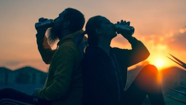 two young people drinking beer during while the sun goes down sunset