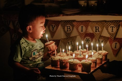 Child blowing out birthday cake under candles