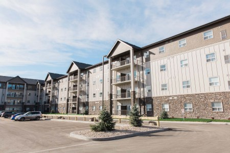 Four floor apartment building with stone siding, vertical siding