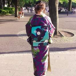 A woman in the back of a purple kimono with a floral pattern