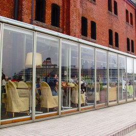 Passenger ship reflected in red brick warehouse glass