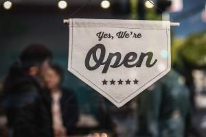"""""""yes, we're open"""" sign on store door"""