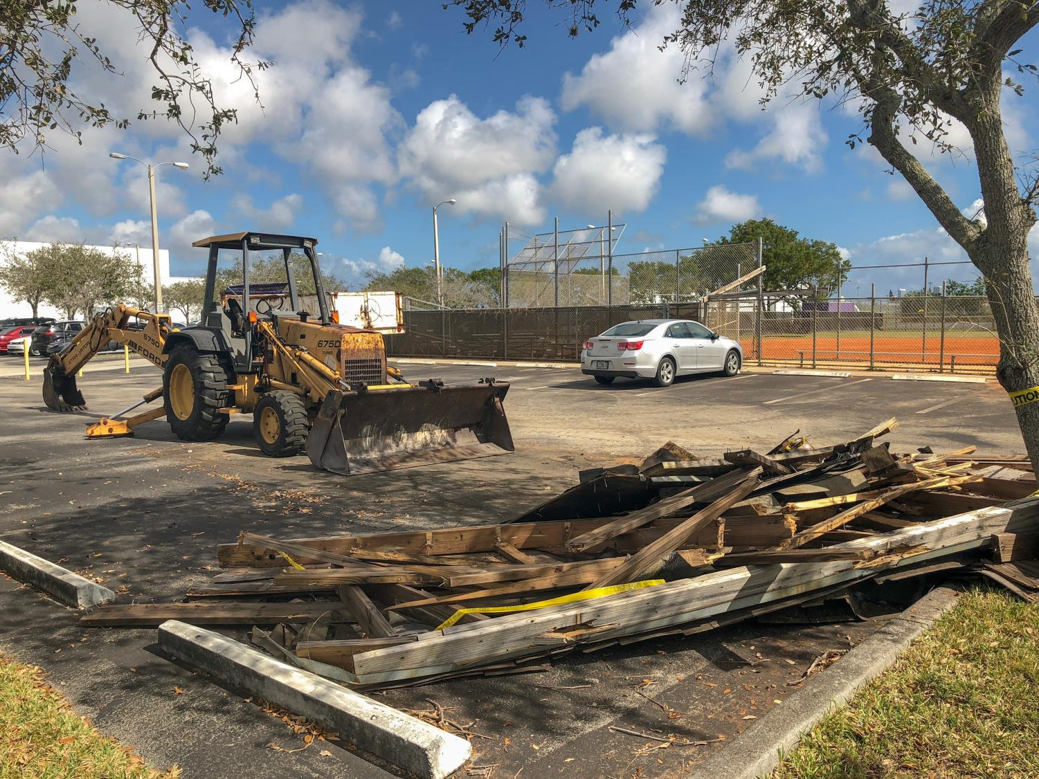 An MDCPS Maintenance and Operations bulldozer clears the student parking lot of the dugout's roof wreckage. The debris had blown away during Hurricane Irma in Sept. 2017.