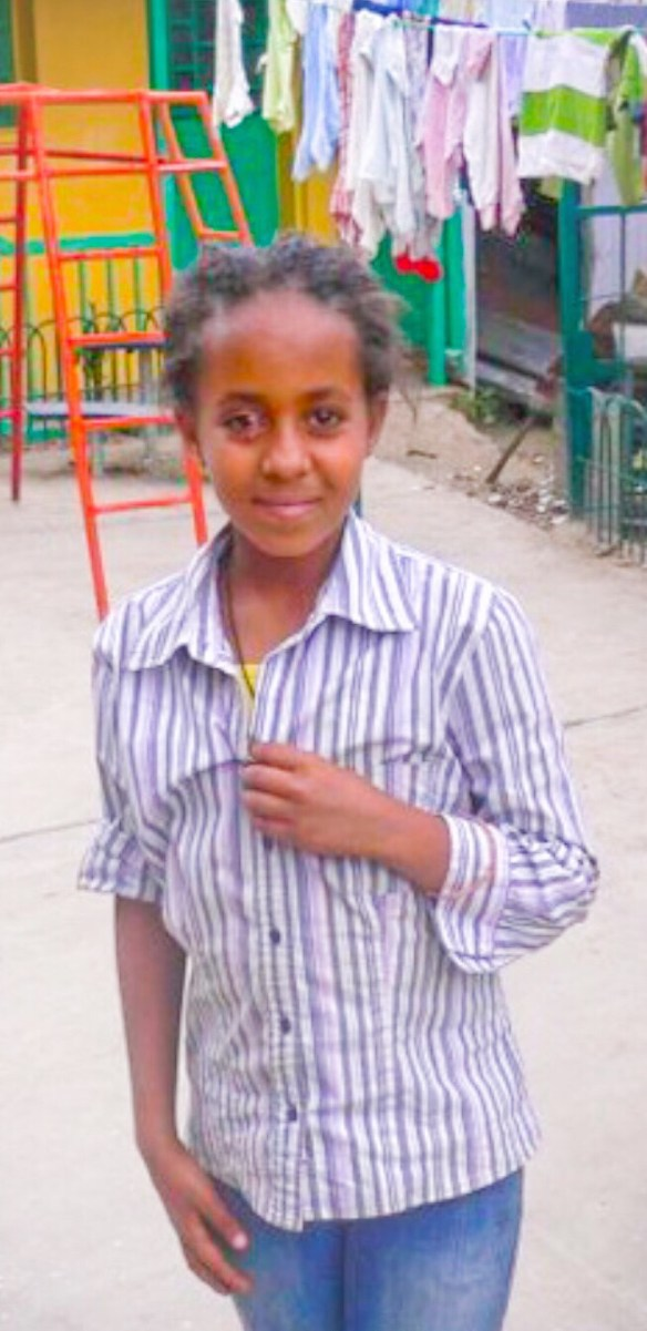 The photo is of Hana when she was in Ethiopia. She is wearing a striped shirt and has a slight smile.