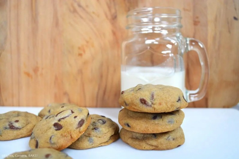 Mrs Fields Chocolate Chip Cookies Copycat recipe. Pile of thre cookies with more chocolate chip cookies scattered around in front of a half full jug of milk.
