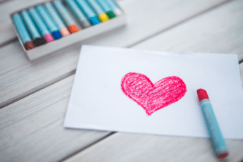 pastel crayons and white paper with red drawn heart