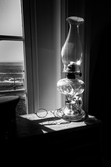 A kerosene lamp an a pair of spectacles sit on a table of the workroom at the Yaquina Head Lighthouse. The lighthouse, constructed in 1872, stands 93 feet tall and is built on a narrow promontory of land sitting nearly a mile out into the Pacific Ocean. It is Oregon's tallest lighthouse. The oil-burning lamp has been replaced with this 1000-watt globe at the Yaquina Head Lighthouse but the light still shines every night to alert mariners to this hazardous stretch of coastline.