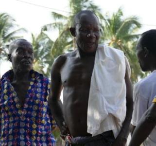 Vanhemmat seremoniamestarit neuvottelevat, mitä valkoihoisten pitää maksaa, jotta voivat osallistua Zangbeto-sessioon ja kuvata sitä.
