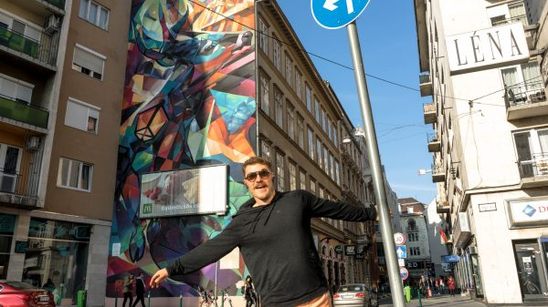 man with moustache glasses and orange shorts posing holding onto a metal pole while posing in front of a large mural on the side of a building in budapest