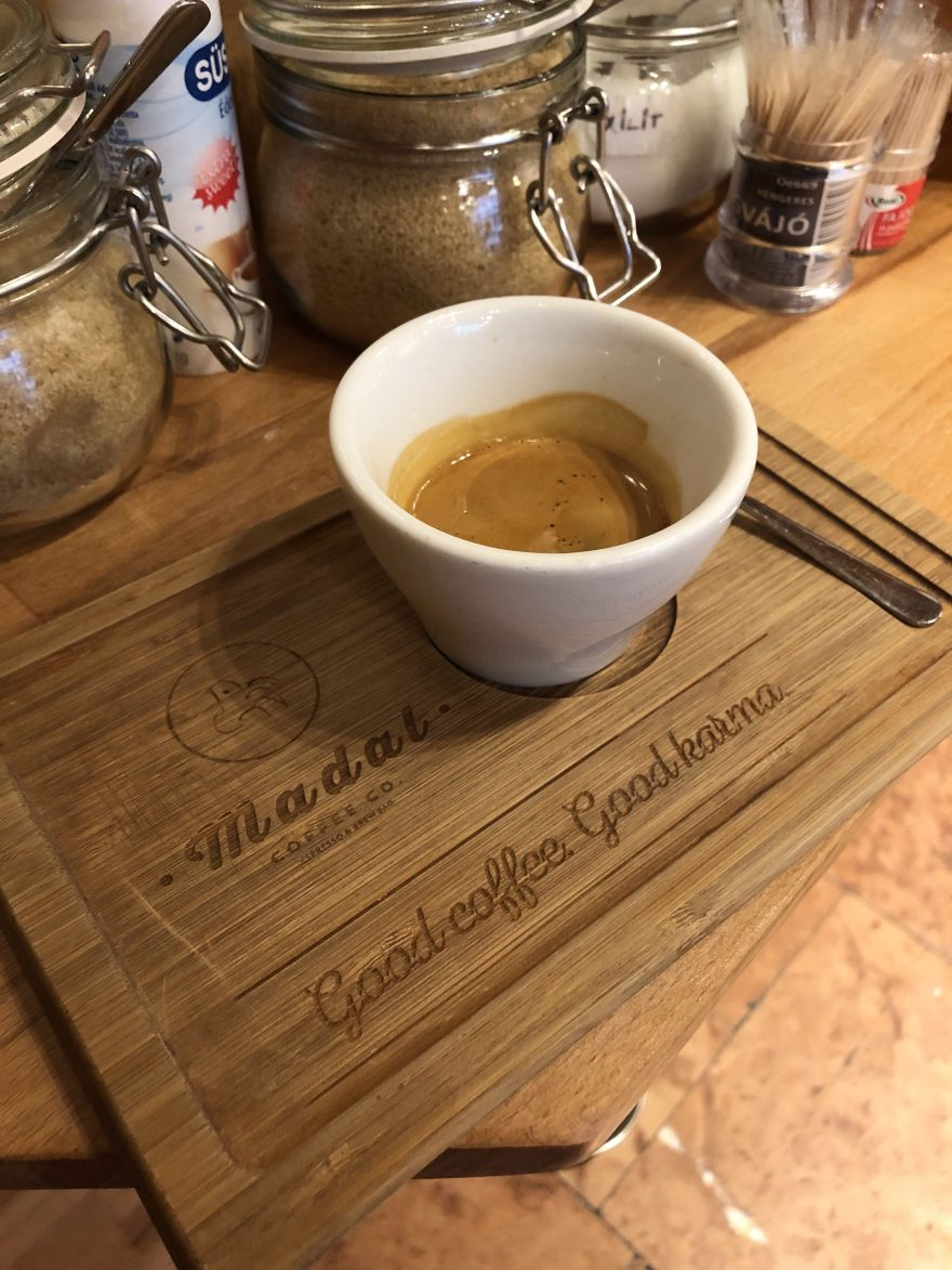 "white cup filled with espresso on a wooden tray that says madal and ""good coffe good karma"""