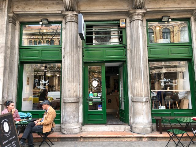 man and women sat outsie coffee shop in budapest with green painted doors and windows