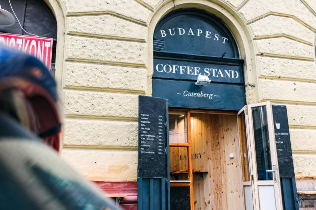 "cream coloured exterior of a coffee shop which has a black sign that says ""budapest coffee stand gutenberg"""