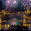 nightime aerial view of st stephens day fireworks at the danube with szechenyi chain bridge margit bridge budapest parliament building in backdrop underneath purple pink and green fireworks
