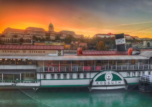 "green white and red boat that says ""kossuth"" and ""venhajo etterem"" in front of buda castle bu"