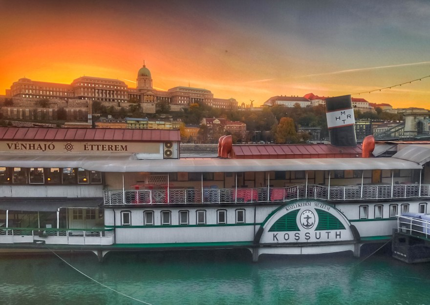 """green white and red boat that says """"kossuth"""" and """"venhajo etterem"""" in front of buda castle bu"""