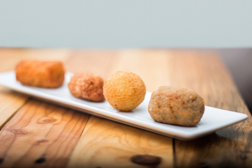wooden-table-with-white-plates-that-has-croquettes
