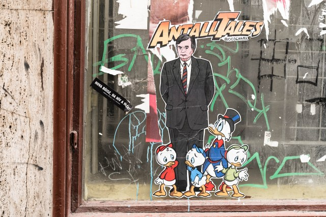 cartoon street art of man wearing suit surrounded by ducks in Budapest's 7th District