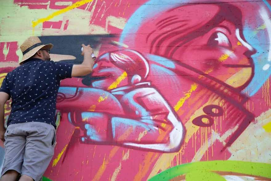 man-with spotted-top-and -straw-hat-spray-painting-graffiti