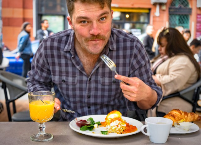 man eating eggs benedict with orange juice in 7th district restaurant