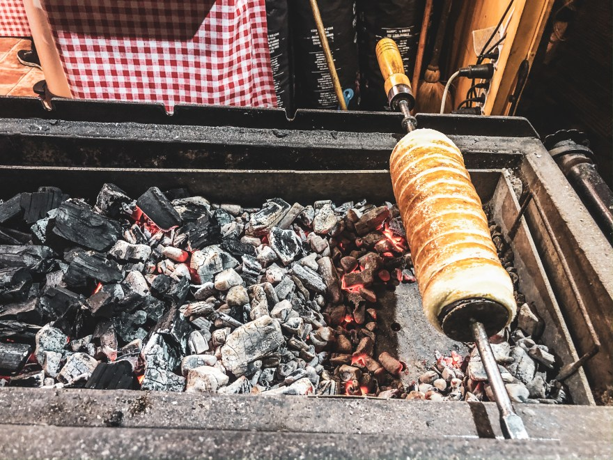 chimney cake on a skewer atop a coal lit fire