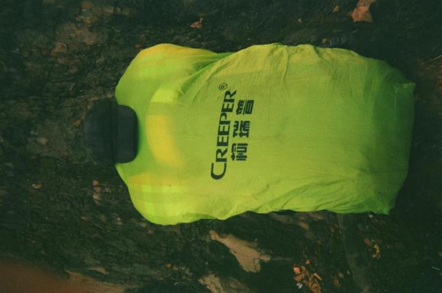 "green highlight vest covering a bag on the floor with writing that reads ""creeper"""
