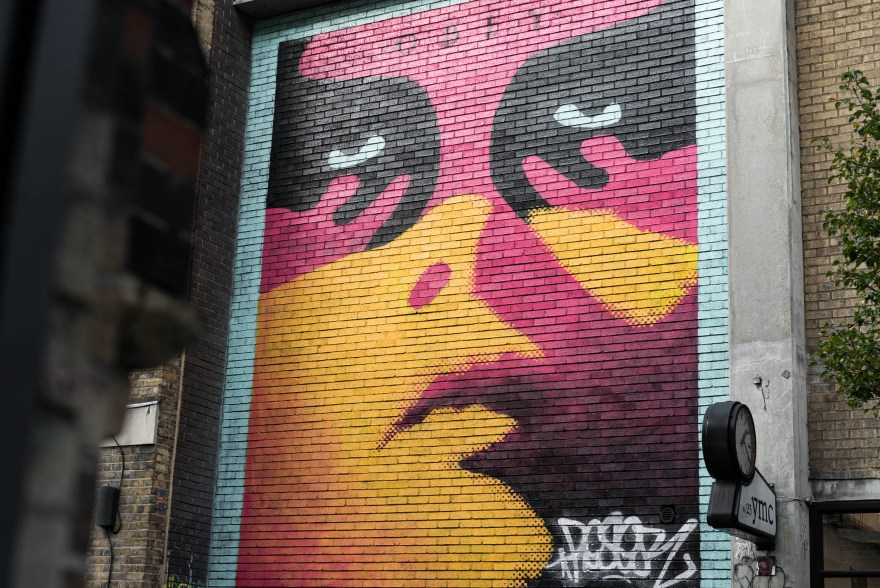 pink and yellow street art in brick lane depicting Shepard Fairey's obey logo