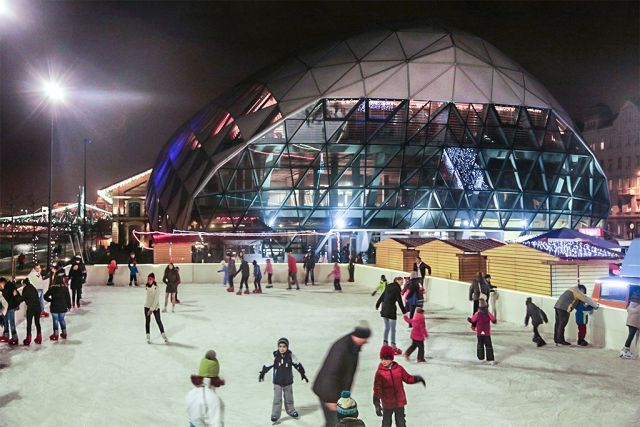 kids-parents-ice-skating-on-outdoor-ice-rink-in-front-of-glass-building