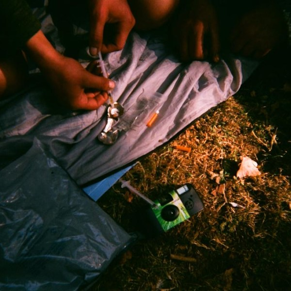 A man with a syringe and metal spoon preparing a hit of heroine
