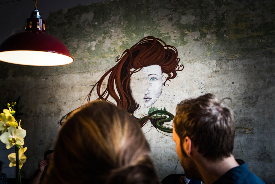 man and women sat inside the goat herder coffee shop in budapest which has a mural of half face a red haired women