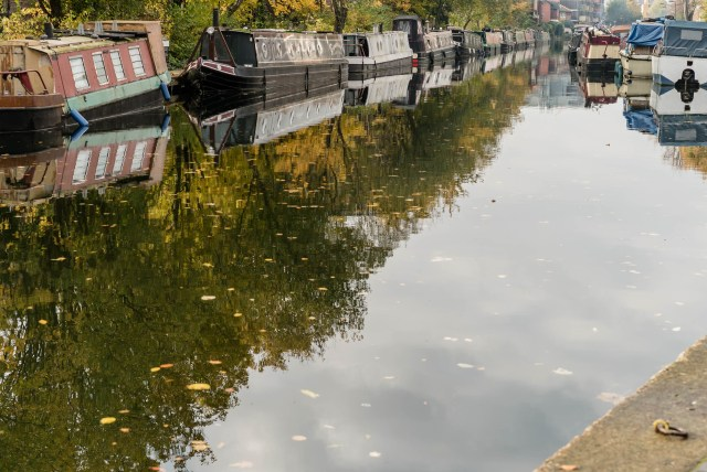 run down narrowboats line the murky green water of regent's canal