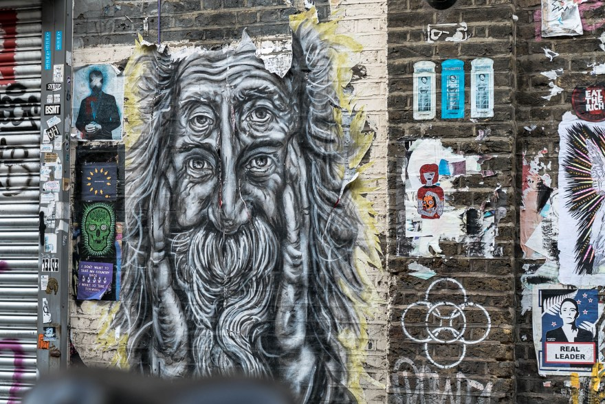 brown wall with stickers and street art depicted an old man with four eyes in brick lane