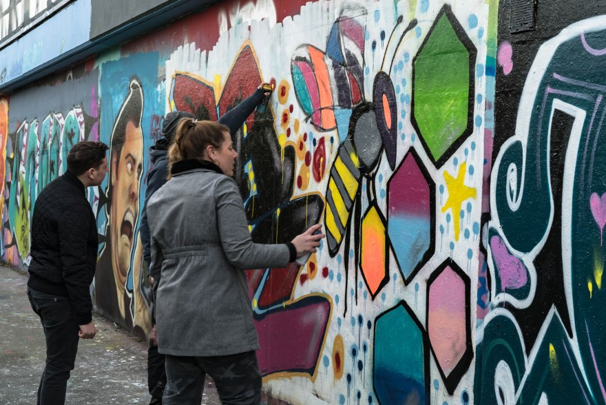 girl looking at spray painted wall which has a bee and other street art with a can in her hand whilst on guy is painting and another guy is wathcing
