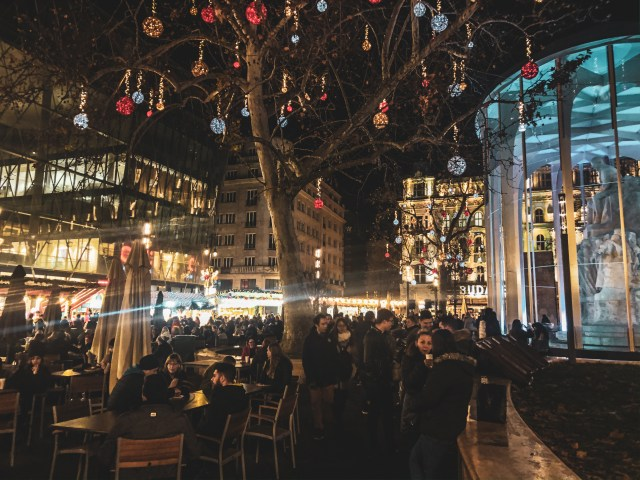 crowds of people gathered under colourfully decorated trees at vorosmarty ter christmas market