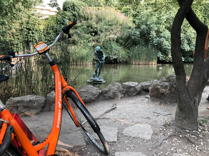 orange bike green pond statue
