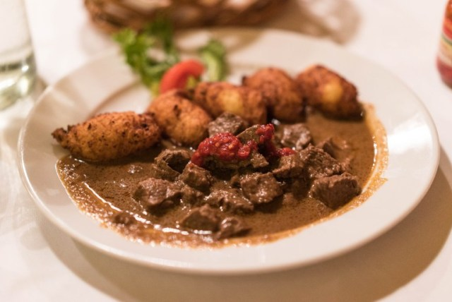 white plate filled with beef gulyás and potato dumplings in a budapest restaurant