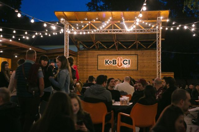 packed outdoor bar in budapest with fairy lights and a wooden stage that has a sign which reads kobuci
