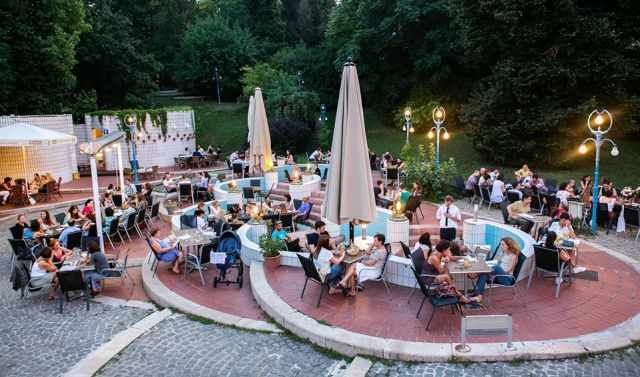 outdoor restaurant and bar terrace with dining tables and chairs inside disused swimming pools in gellert baths budapest