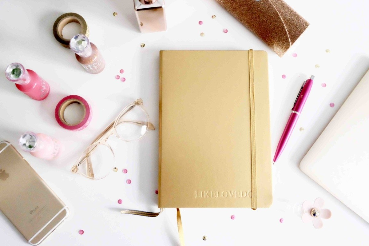 desk space flat lay pink gold glitter embossed leather journal