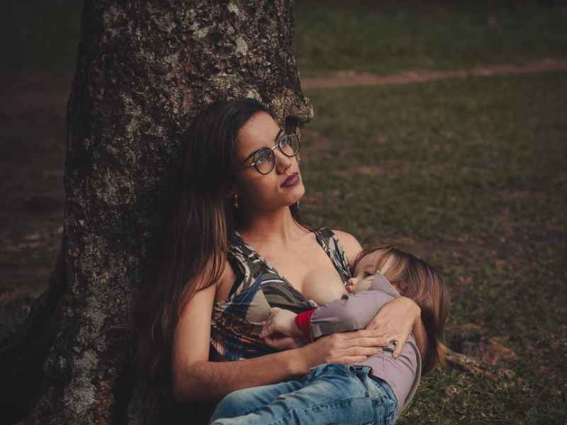 photo of woman breastfeeding her toddler under the tree
